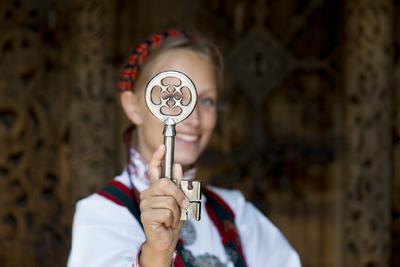 Kvinne i drakt viser nøkkelen til Gol stavkirke