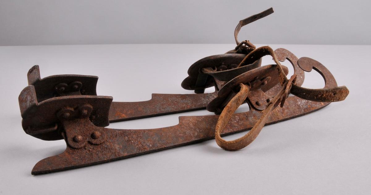 Smidde jarnskeiser med bua tupp. To plater til å ha foten på og skinnreimar til feste over tåpartiet.