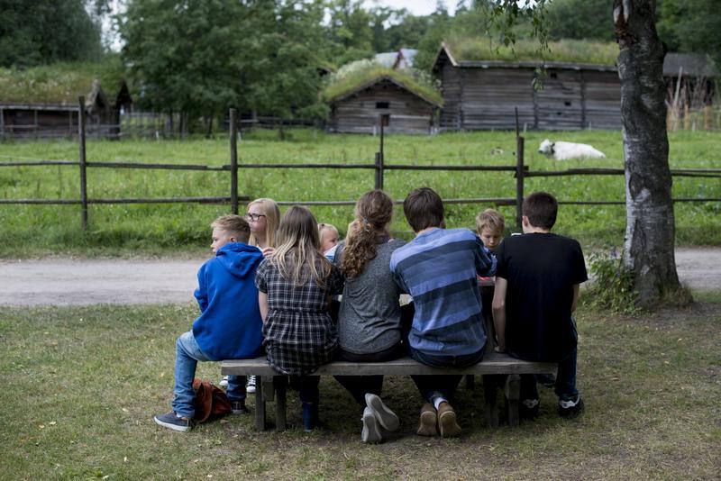 Gruppe barn og unge sitter rundt piknikbord