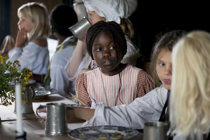 Barn på Ferieskolen ved bordet under måltid.