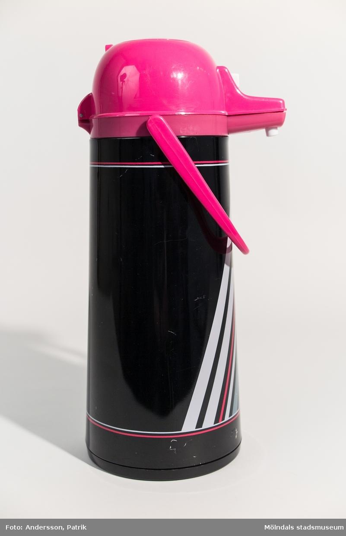 Pumptermos från 1980-talet.  Termosen är svart med ränder i grått och cerise. Locket och handtaget är också cerise.