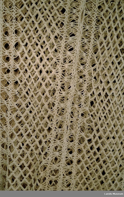 Heklet teppe bygd opp av luftmasker og staver i eit mønster. Frynser rundt heile kanten.