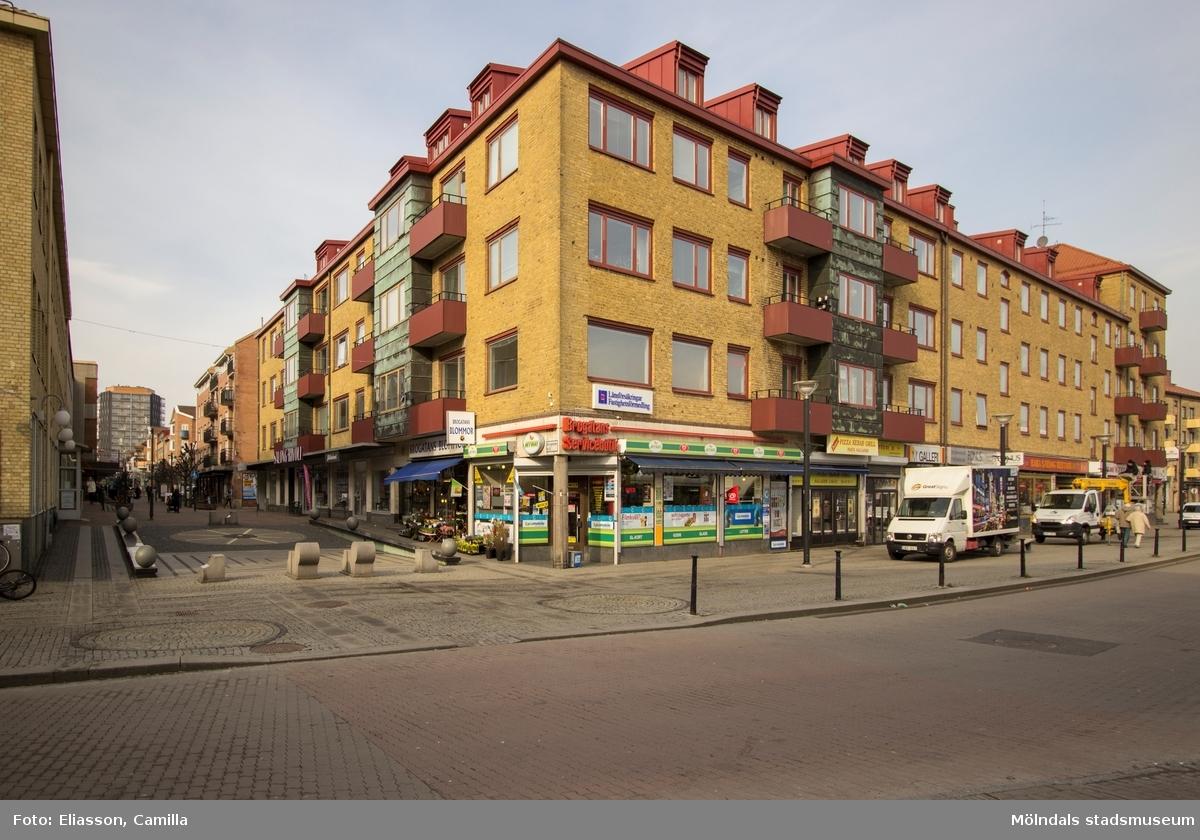 """Mölndals centrum sett från Broplatsens buss- och spårvagnshållplats. Frändbergska huset kallades länge """"Centrumhuset"""" och ansågs vara hjärtat i Mölndals nya köpcentrum. Det byggdes i två omgångar, den vänstra delen uppfördes 1937-1938 och den högra 1952. Olyckligtvis byggdes huset med källare i ett av Sveriges mest översvämningsdrabbade områden. Huset ligger i början av Brogatan (tidigare Frölundagatan). Det kommer att bevaras även vid nybyggnation. I slutet av Brogatan syns höghuset på Storgatan 32A."""