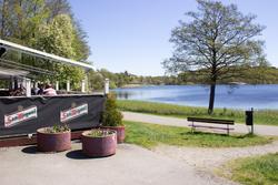 """Vy från Restaurang Stensjön utöver Stensjön. Skyltar med """"Sa"""