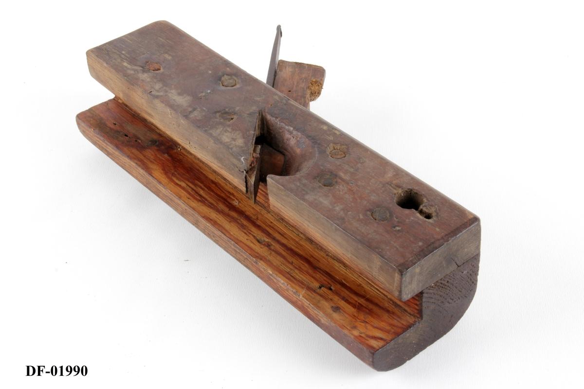 Høvel med kile og blad. Høvelstokk i to deler og av to tresorter, sammenføyd vertikalt og på langs med nagler. Avstand styrelist-jern er 2 cm. Vinkel for høveljern er 46 grader. Gjennomboret hull i forkant.