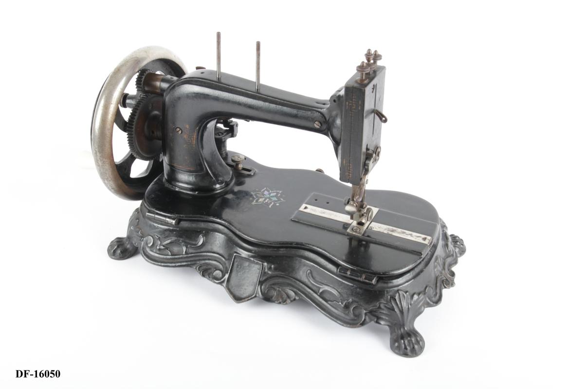 Symaskin med håndsveiv montert på en metallsokkel med løveføtter.