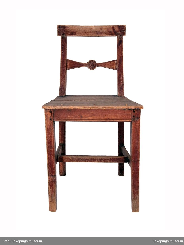 Stol i tappkonstruktion med sitsen vilande på en sarg. De bakre benen är förlängda och bildar en del av ryggstödet. De förenas upptill av ett rakt överstycke och en bit ner av en profilerad tvärslå. Den senare smalnar av mot mitten och sväller där ut i en rundel med skuren ornamentik som liknar ett solhjul. Sitsen är något smalare bak än fram och är dessutom ett par centimeter kortare än sargen bak. Benen förenas nedtill av tvärbjälkar som bildar ett H. Stolen har satts ihop med träplugg. Den har varit brunmålad.