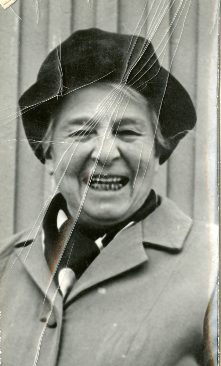 Dame med hatt og kåpe avbildet foran en vegg. Kvinnen har skjerf i halsen.