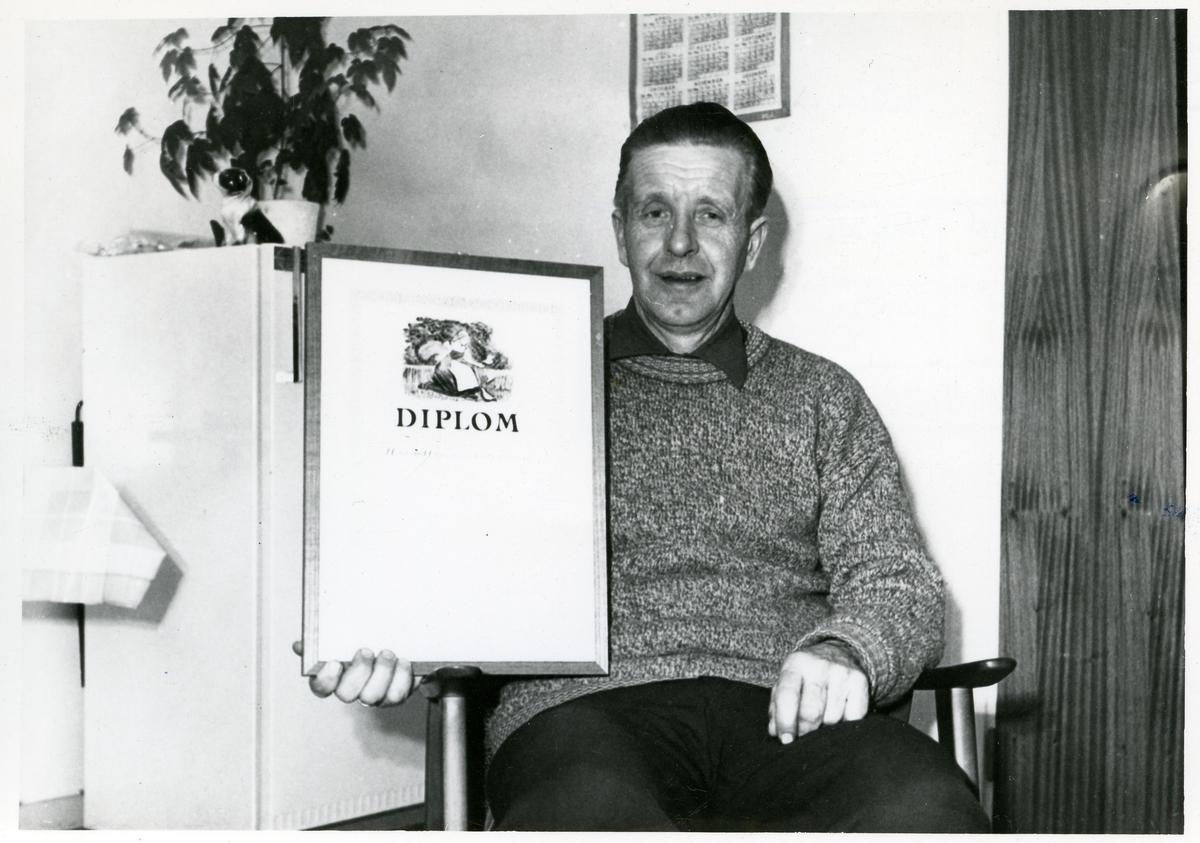 En mann sitter i en stol og viser frem et diplom.