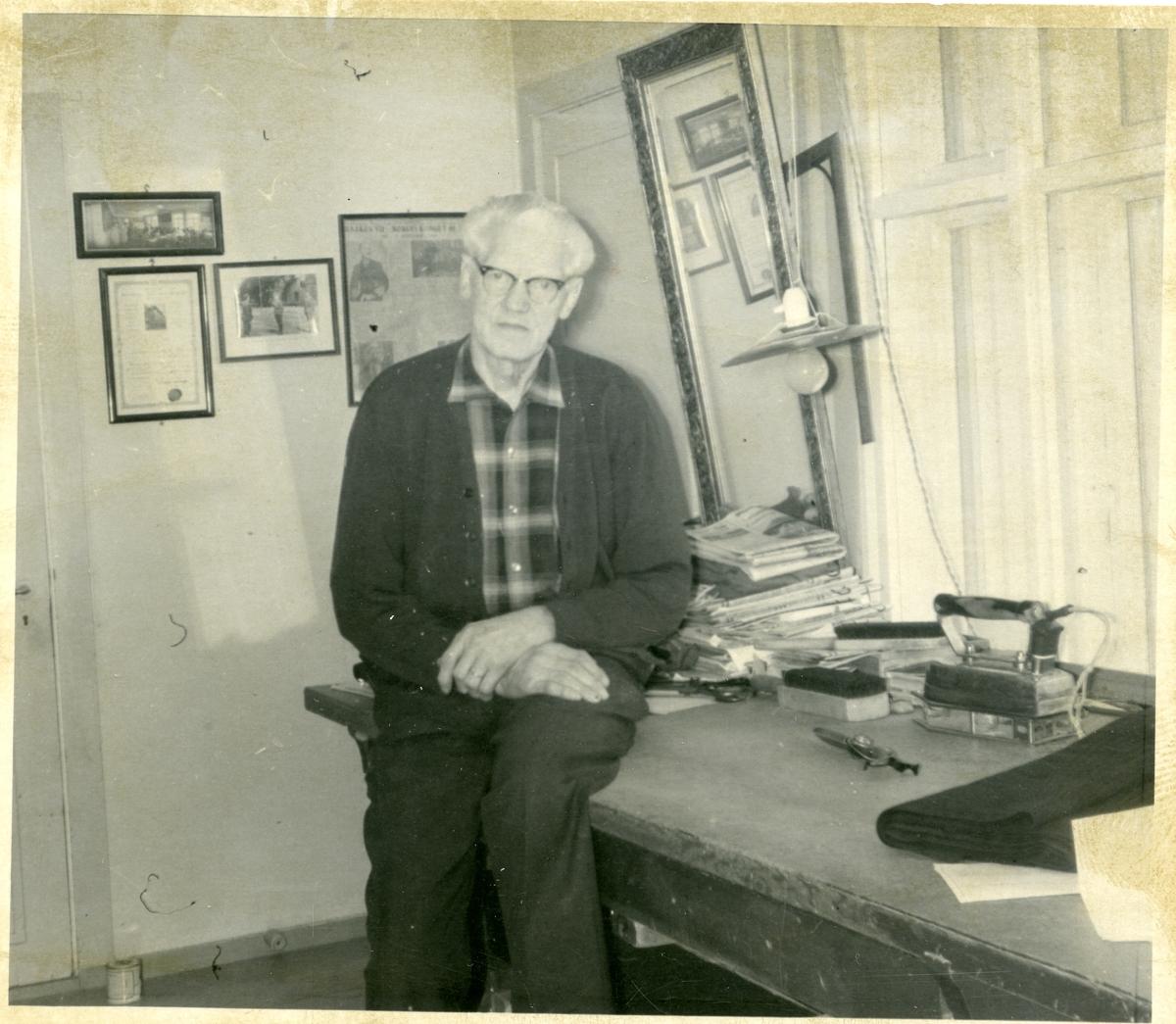 En mann sitter på et skrivebord. På veggen henger det bilder og et speil.