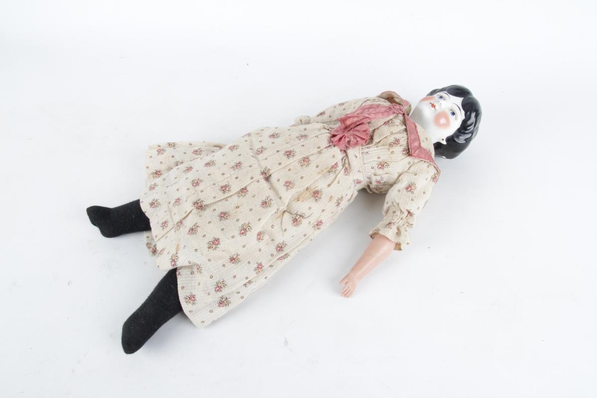 Porselensdukke med svart hår, kledd i blomstrete kjole.