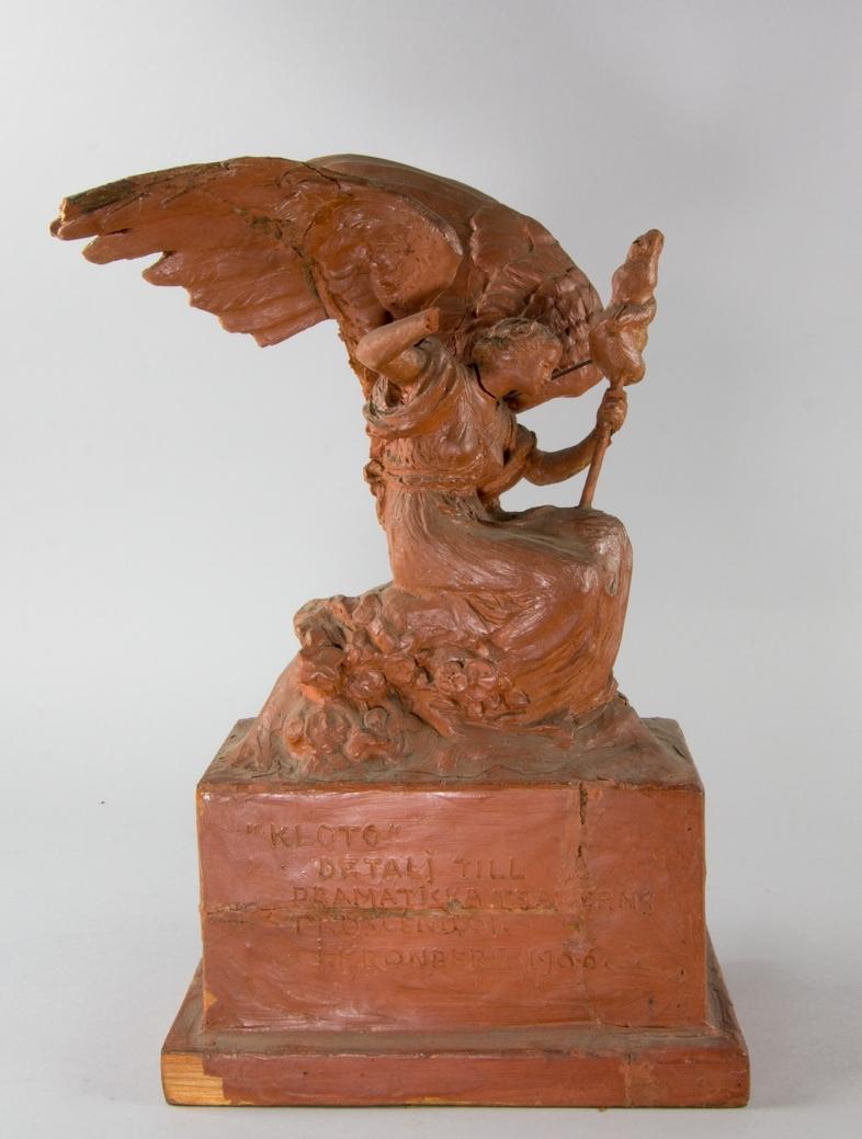 Kloto, en av ödesgudinnorna, med utslagna vingar som spinner livets tråd. Sitter på blomsteromgärdad kulle på hög sockel.