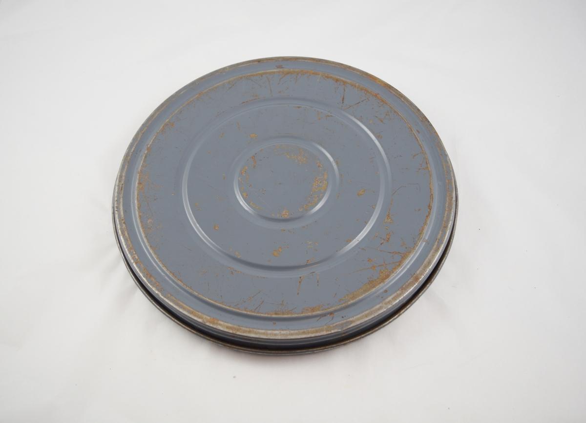 Filmrull i eske. Film på metallspole. Rundt metalletui i to deler: bunn og lokk.