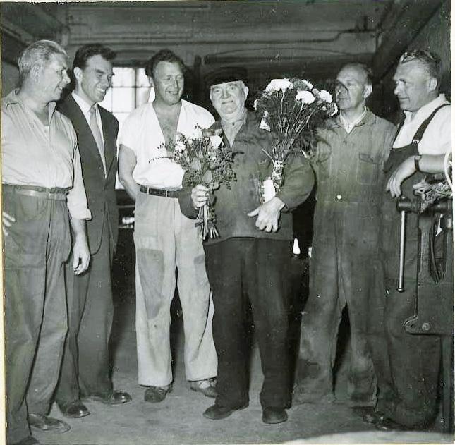 """AB Papyrus.  Sven """"Sme-Sven""""Svensson  uppmärksammas med blomma från kollega. 30/6 1956. Omgiven av fem kollegor. Okänd, Nils Nilsson, Okänd, Sven Gustaf Svensson, Ossian Forsell och Okänd."""