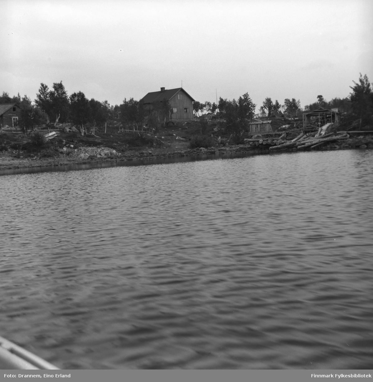 Bilde tatt fra innsjøen mot et hus og noen hytter langs bredden.
