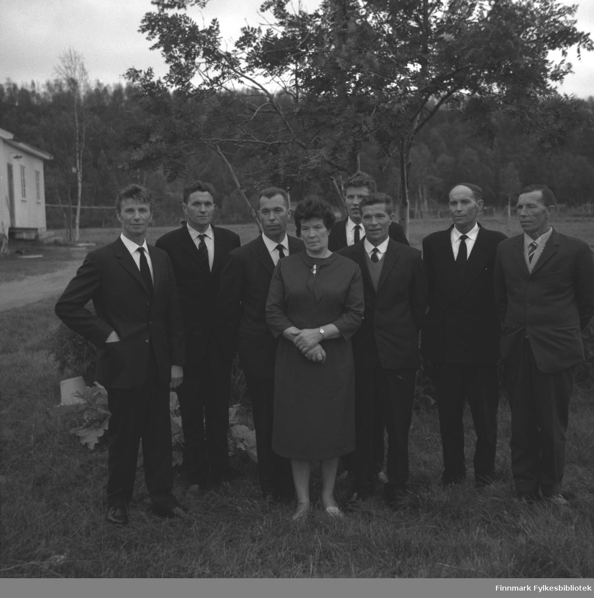 Syv menn og en dame poserer for fotografen på et jorde i Neiden. De er fra venstre: Eino Drannem, Hermann Karikoski, Gunnar Karikoski, Lyyli Arvola, Oskar Karikoski, Aage Karikoski, Helge Karikoski og Arne Karikoski.