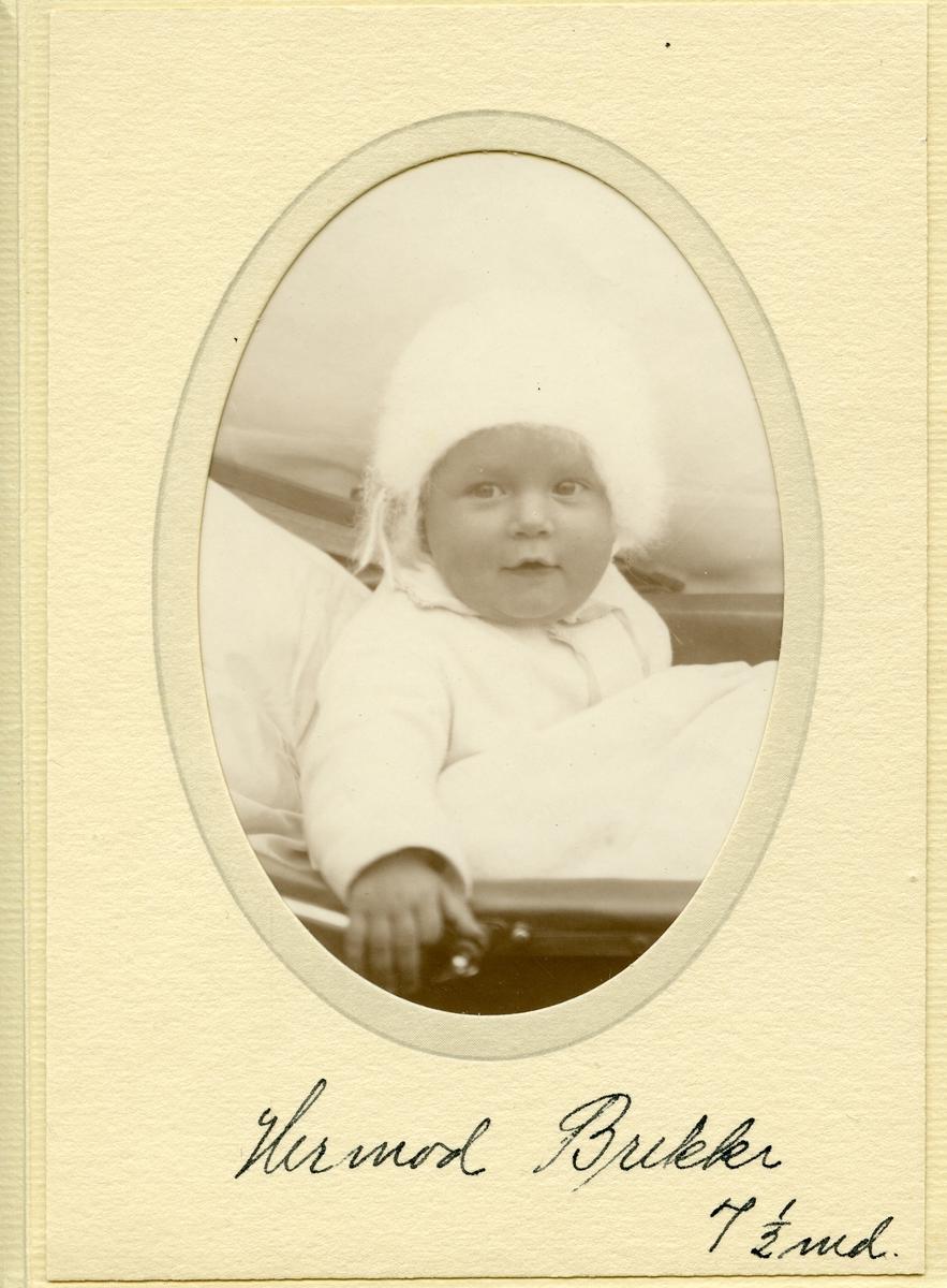 Liten baby sitter i barnevogna. Han har på seg en hvit lue og sitter under en dyne.