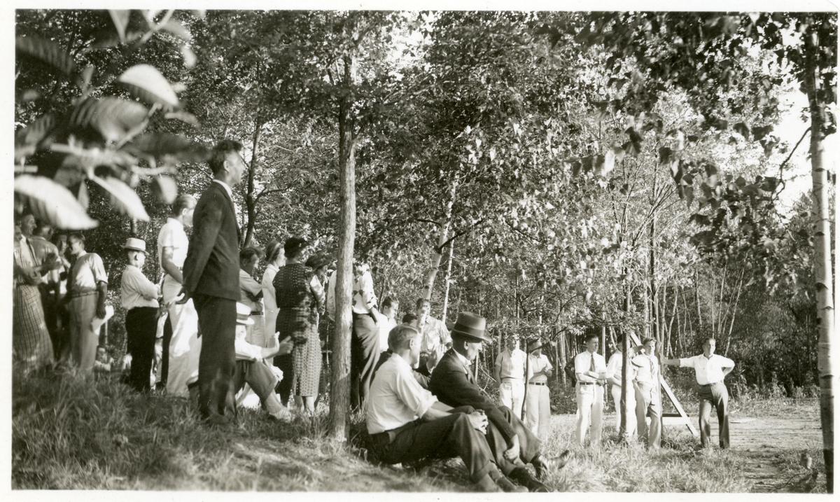 Bildet viser kvinner og menn som tilhørere/publikum. De står under noen trær i en park (?) Bildet er tatt i forbindelse med et stevne i Amerika i 1934. Alle er kledd i pent sommertøy. Olaus Islandsmoen sitter foran med hatt.
