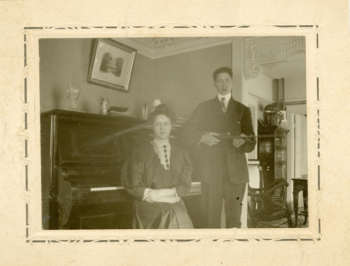 Bildet viser en ung kvinne sittende ved et piano og en ung mann stående ved siden av. Mannen holder en fele/fiolin under armen. Dette er norskamerikanere og foto er tatt i USA.