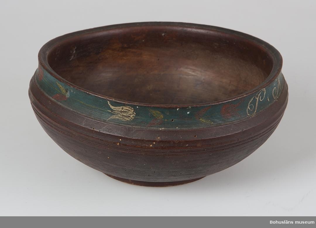 Rund skål, svarvad ur rått björkträ, inuti partiellt bearbetad med skölpjärn. Linjedekor, en något indragen öppning och med fotring.  På utsidan målad i brunt, det övre bandet i blått dekorerat med rosmåleri i rött, vitt och blått av tulpaner och motstående initialerna PNJ och AND.  Svarvad och bemålad skål, en s.k. bolle av västsvensk tillverkning från omkring 1750 – 1850.  Skålen är mycket välbevarad.