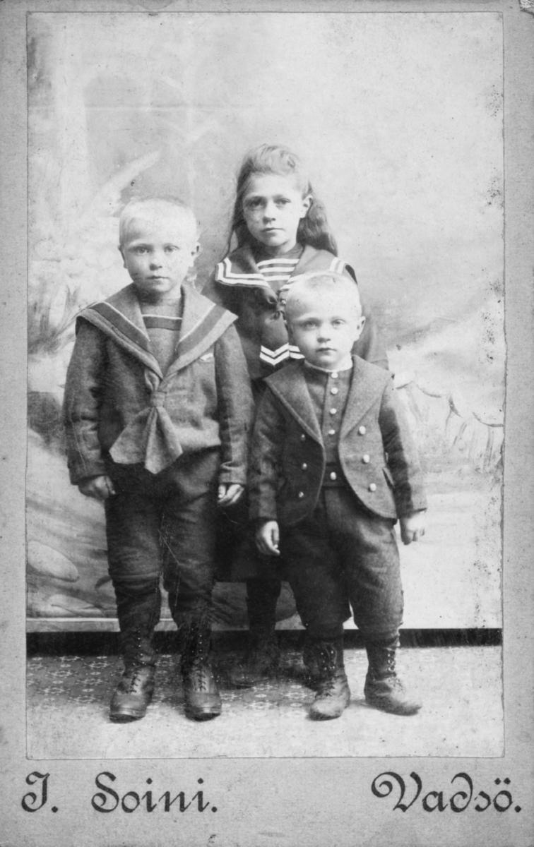 Visittkortportrett av to gutter og en jente, antagelig søsken. Jente har en matrosekjole på seg og den gutten en matrosedress.