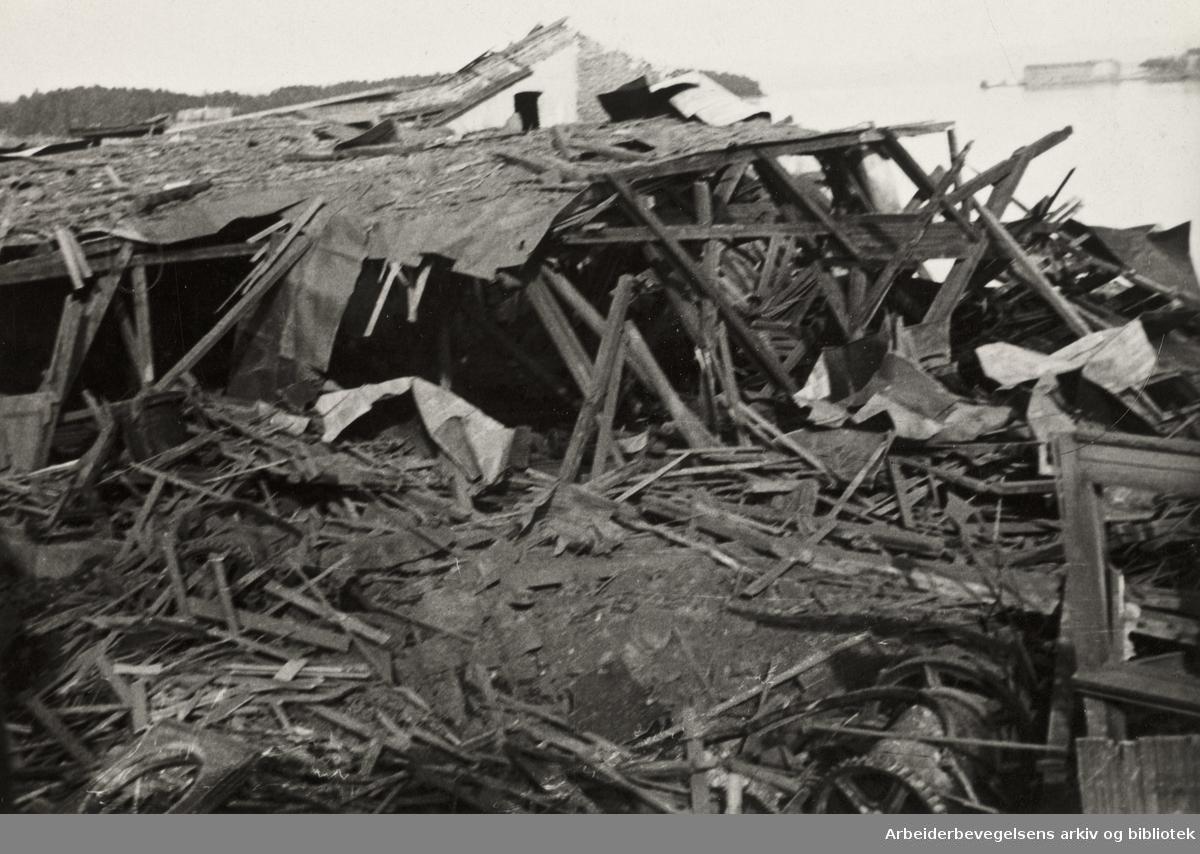 """Ole M. Engelsens fotografier fra okkupasjonsårene i Oslo..Filipstad-ulykken 19. desember 1943. Eksplosjon og etterfølgende brann i et kullopplag på havneområdet Filipstad og nærliggende boligområder på Skillebekk i Oslo..""""Materialskur - pinneved"""". ."""