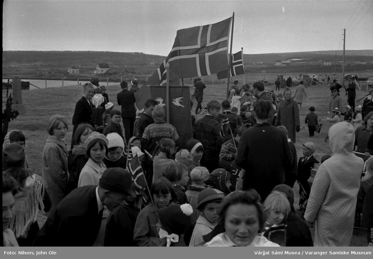 17. mai feiring utenfor Nesseby kirke i 1967.Toget gjør seg klart til å gå opp mot Nesseby skole. Fra venstre: Nils Anders, Ruth, Synnøve, Astrid og Ellinor Nilsen, Grethe Store, Kurt Johnsen og Kjell Andersen.