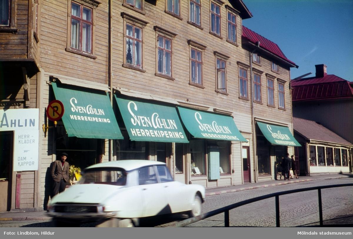 Vy från Papyrus port mot byggnader vid Kvarnbygatan i Mölndal, 1960-tal. Från vänster ses Sven Ahlin Herrekipering med adress Kvarnbygatan 25 och C.J. Johanssons Järnhandel med adress Kvarnbygatan 27.  För mer information om bilden se under tilläggsinformation.