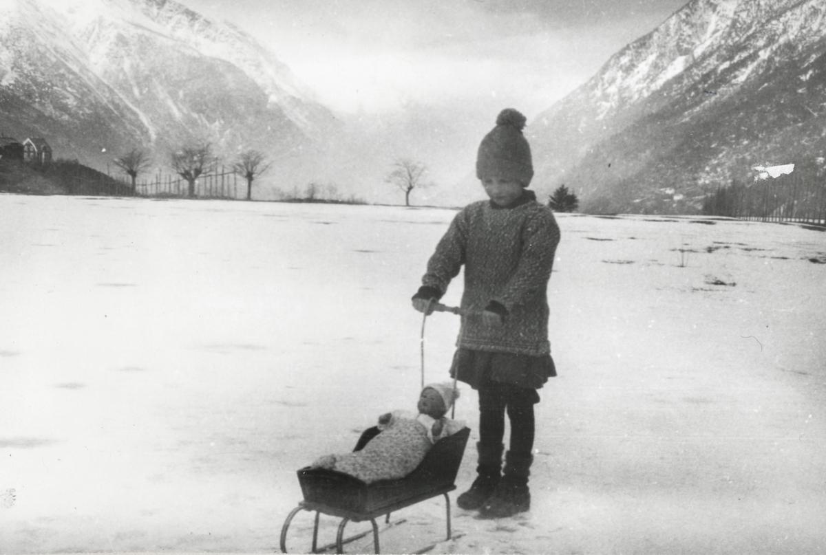 Ei jente, vinter, snø, strikkaklede, strikkahue, i bakgrunnen dokkeseng på maiar t.v.  hus på Toppen,