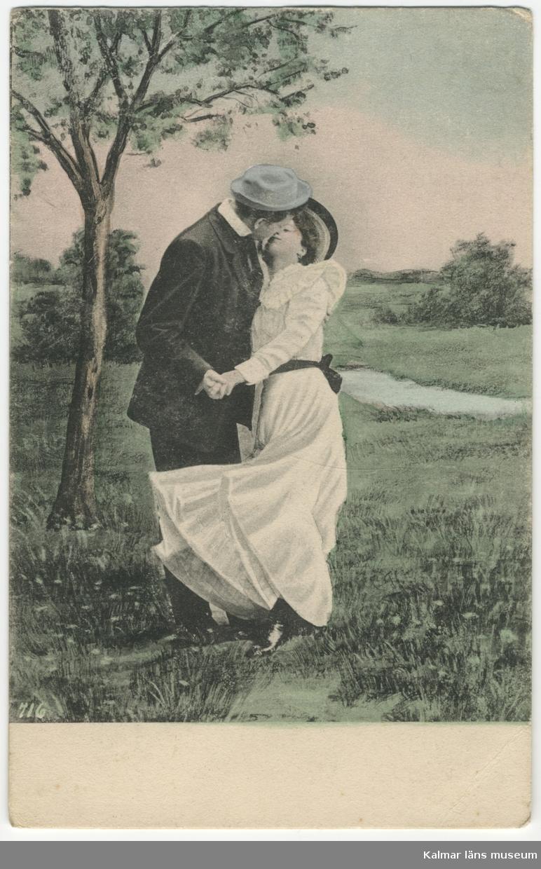 En man kysser en kvinna ute i en park eller liknande. Hon har hellång vit klänning.