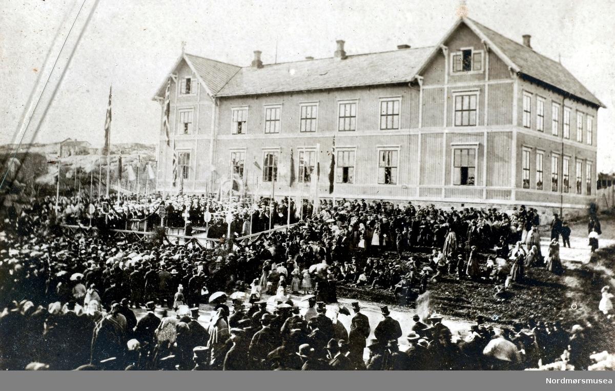 """Her ser vi den første sangerfest i Kristiansund, pinsen 1873 hvor kor fra Molde, Ålesund og Kristiansund deltok.  Konserten ble holdt foran den nye latinskolebygningen.  Sangerne er oppstilt i en innhegning opp på """"lærerpromenaden"""" sør for bygningen, omgitt av unionsflaggene.  Svart av tilhørere nede på plassen og på resten av lærerpromenaden.  Åarasoller og flosshatter!  I bakgrunnen til venstre skimter en den gamle bebyggelsen på Lyhshaugen, der kirken ble reist i 1878.   (Fra Nordmøre Museum sin fotosamling.) EFR2015"""