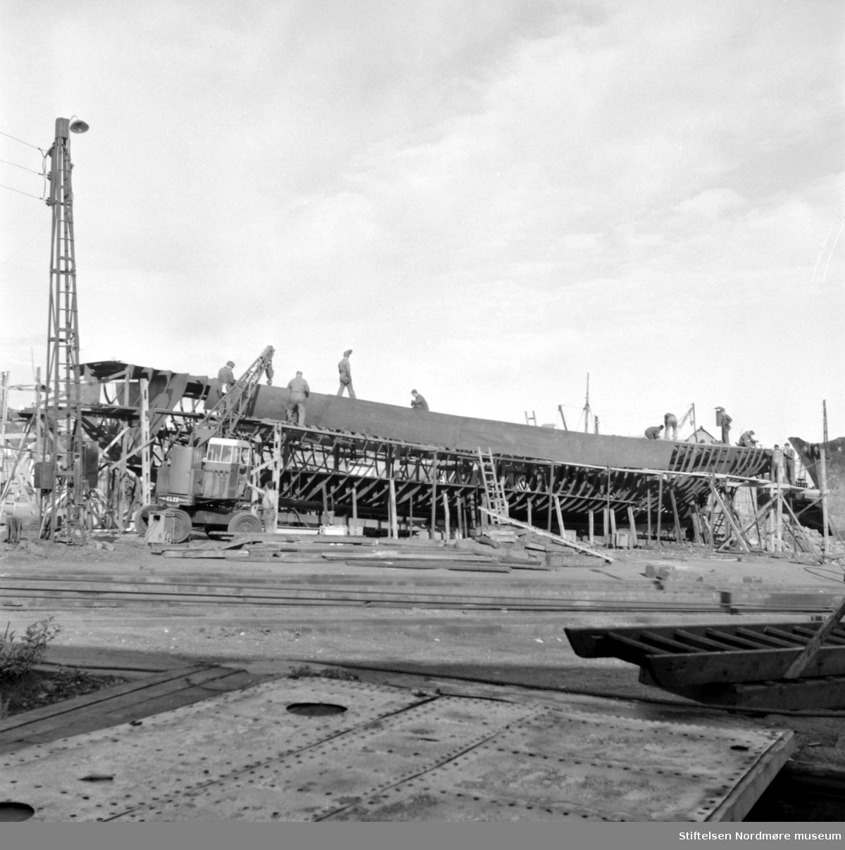 """Bildet viser B/F"""";Norddalsfjord""""; bnr.14 på beddingen ved Storviks Mek. Verksted. """"Norddalsfjord"""" ble levert til Møre og Romsdal Fylkesbåtar 15. mars 1961 og hadde følgende hoveddimensjoner: L 31,20 m x B 8,55 m x D 3,35 m og hadde en tonnasje på 159 bruttoregistertonn. Fremdriftsmaskineriet består av 3 Volvo Penta turboladede dieselmotorer type TMD96 på til sammen 420 hk som via kilremdrift var koblet til et felles gir og propellaksel med vribar propell, slik at hver enkelt av motorene kunne kjøres separat. Fergen hadde 2 Bolinders vekselstrøms-aggregater type 1052MG på 23 hk hver tilkoblet en generator på 17 kW. Fergen var utstyrt med elektrohydraulisk styremaskin. Fergen har plass til 18 personbiler og har sertifikat for 160 passasjerer. Forut er det innredet 6 lugarer for offiserer og restaurantpersonale og akterut en mannskapslugar for 4 personer og toppfarten er 11,4 knop og marsjfarten 10,5 knop. Ferga er verkstedets første nybygg etter B/F""""Trygge"""" som ble levert i 1938.  Foran nybygget ses verkstedets mobilkran av fabrikat Jones KL22 innkjøpt ca. 1959. Den hadde en 1-sylindret dieselmotor til drift og hadde en maksimal løfteevne på 2 tonn og kjørte på bildekk, med solide stålfelger til å avlaste dekkene ved løfting. Helt til høyre ses baugen på hvalbåten """"Star X"""" som ble ombygd til kraftblokksnurper ved verkstedet og fikk navnet M/S""""Nordbas"""" og ble en av de største i Norge. Til venstre for """"Star X"""" og over akterenden på nybygget ses huset til verkstedets dampkjel. Man ser flere ukjente personer som arbeider på nybygget. Personen til venstre for kranbommen til mobilkrana er platearbeider Per Hansø og til høyre for ham ses platearbeider Leif Lesund og utenfor kranhuset ses sjåfør Kåre Frisvold. Personen, lengst til venstre, på dekket, med sveiseskjerm, er platearbeider Jarl Johansen. Personen inne i kranhuset er sansynligvis sjauer Gunnar Pedersen. I forgrunnen ses kjørebroen over slippwiren like ved slippspillet og man ser at den nye patentslippvogna, den stø"""