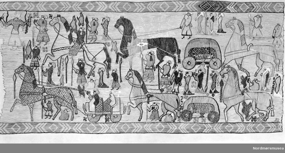 Foto av teppe som er funnet i Osebergsskipet. Osebergdronningen ble gravlagt i en skipsgrav år 834 (tidlig vikingtid). Hennes skip var usedvanlig vakkert dekorert, det var mer et representasjonsskip enn et bruksskip. Da dronningen ble gravlagt, bragte hun med seg i sin grav en mengde fine gjenstander: en vogn, fire sleder, mange hester, telt, rikelig med mat og et rikt utvalg av jordbruks- og husholdningsutstyr. Dronningen var godt forberedt på en lang reise til livet etter døden. Osebergfunnet er det rikeste gravfunn fra vikingtiden selv om graven er røvet. Antagelig har gravrøverne bare lett etter verdisaker og ikke interessert seg for tre, lær og tekstiler.  Det ble også funnet fragmenter av billedtepper med ulike motiver: en prosesjon, en scene fra et slag, menn og kvinner, ulike symbolske tegn. Fragmentene er i svært dårlig forfatning, egentlig er det ganske utrolig at tekstiler i det hele tatt har overlevd oppholdet i leire og jord i nesten 1200 år. Ikke desto mindre gir de kunnskap om den tids vevkunst.  Billedscener fra vikingtiden er svært sjeldne, Osebergfragmentene er et unntak som understreker hvilken rik kulturskatt Osebergfunnet er. Originalene som er utstilt i Vikingskipshuset på Bygdøy vitner om fremragende håndverk. Detaljene i teppet er så fine, trådene i teppet så tynne, vevingen av mønsteret så grann og fin, at kunsthåndverkere i dag neppe kan lage maken selv med vår tids tekniske innsikt. Så vel kunsterisk utforming som håndverk er førsteklasses. Arkeologer har rekonstruert og satt sammen enkelte fragmenter til et hele som gir oss et inntrykk av hvordan originalen kunne ha sett ut. (Kilde: Vikingskipsmuseet Norge).  Fra Nordmøre Museums fotosamlinger.