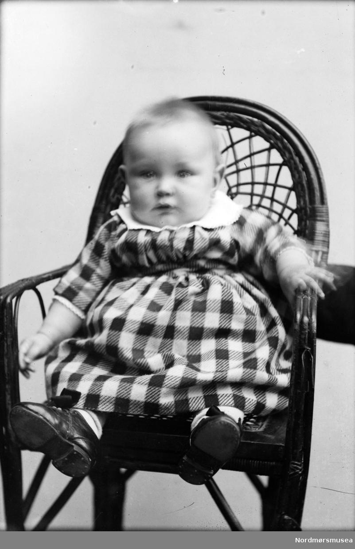 Portrett av et spedbarn sittende i en stol. Muligens fra Sverdrupfamilien/slekten, eventuelt fra deres bekjentskaper. Datering er ukjent, men trolig omkring 1920 til 1930. Fra Nordmøre museums fotosamlinger. EFR2015