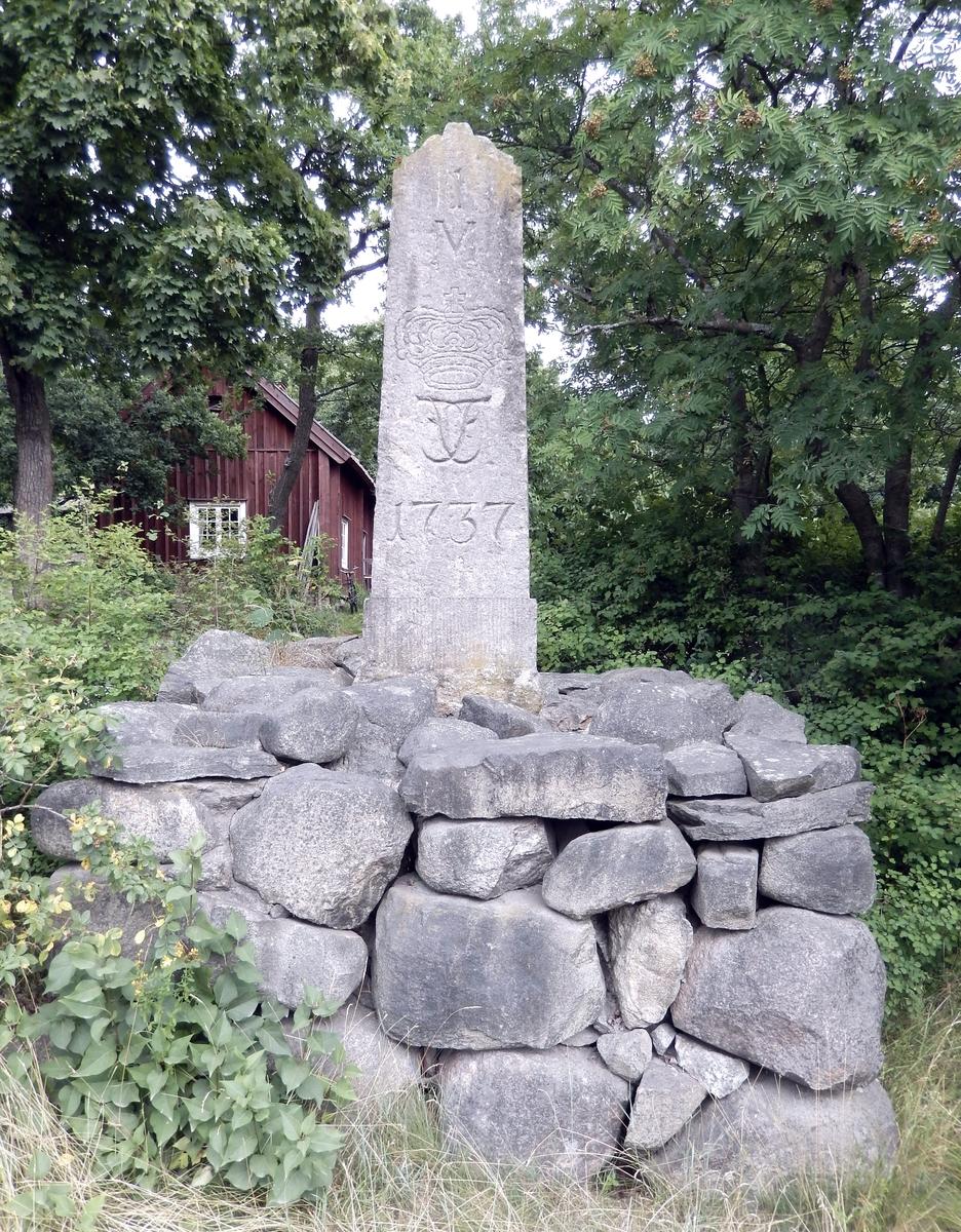 Helmilstolpe i sten från 1737 med krona och kungamonogram (Fredrik I)