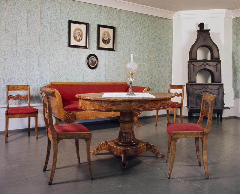 Interiør; brunt bord med stoler og sofa i samme treverk og med rødt trekk, to gamle fotografier på veggen og en etasjeovn i støpejern.
