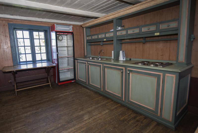 Kjøkkenbenken med oppvasskummer og kokeplater, samt kjøleskapet.
