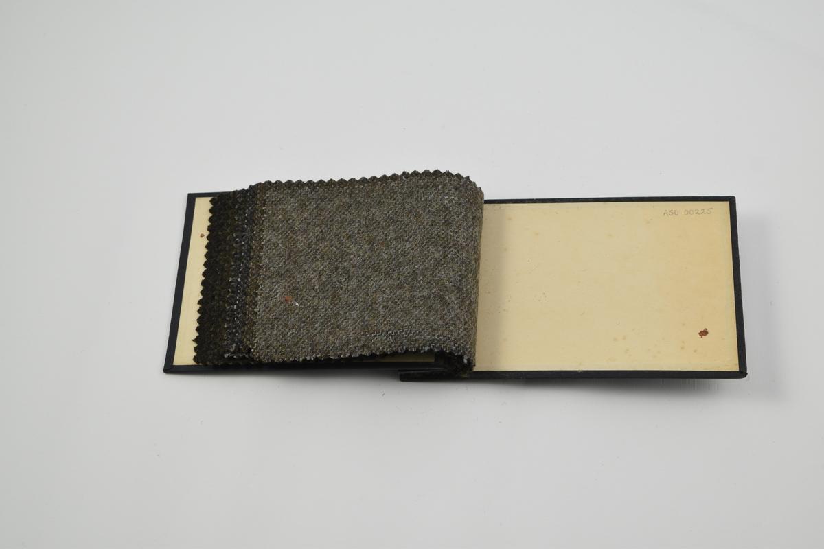 Prøvebok med 8 prøver. Tynne ullstoff uten utpreget mønster i mørke grå og grønne fargetoner. Alle stoffer er merket med en rund papirlapp festet med melallstifter hvor nummer er påskrevet for hånd.   Stoff nr. 545 (grønn), 563 (grønn), 780 (grønn), 781 (grønn), 782 (grå), 783 (grå), 784 (grå-grønn), 785 (grå).