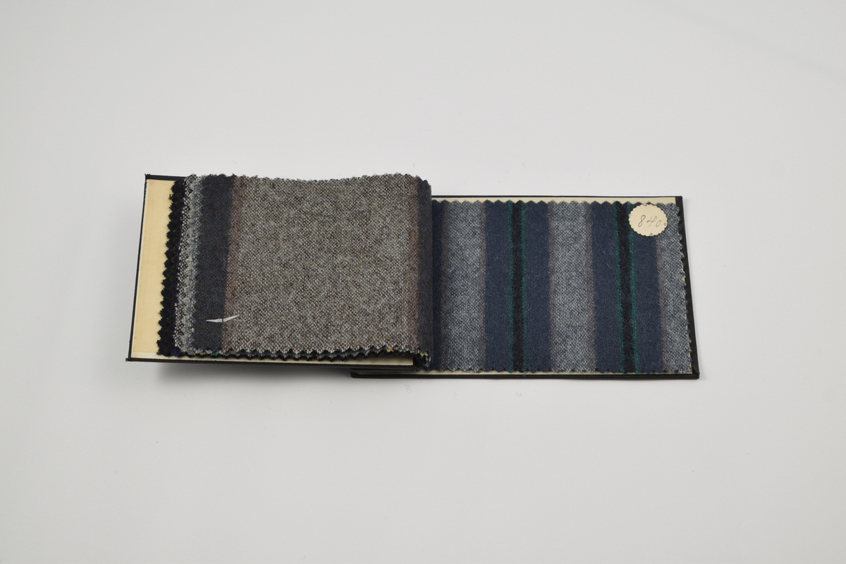 Prøvebok med 8 prøver. Tynne ullstoffer i blå-grå farger. Stoffene har mønster av vertikale striper i ulike farger. Alle stoffer er merket med en rund papirlapp festet med melallstifter hvor nummer er påskrevet for hånd.   Stoff nr. 827 (blå), 828 (mørk brun), 829 (grå), 837 (grå), 838 (blå), 839 (blå), 840 (blå), 841 (grå).