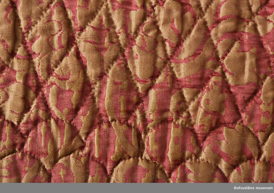 Färg: rosa och gulbrunt. Detta täcke lär från första början ha varit en brudunderkjol (stubb) åt Ingrid Johnsdotter, född på Björkö år 1762. Blev därefter omsytt till brudtäcke åt dottern Johanna Andreasdotter då hon år 1821 gifte sig med Lars Christenson på Öckerö. Har tillhört deras dotter Ingrid Larsdotter som gifte sig 1849 med Olof Bryngelson Utbult, Öckerö. Givaren är sjätte generationens ägare.