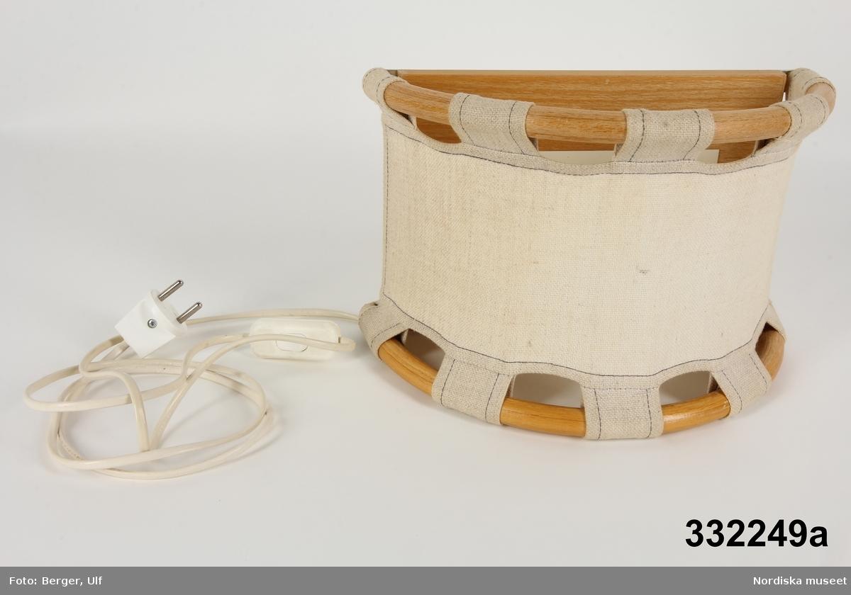 Vägglampa, halvcirkelformad. Platt bakstycke av trä med konvex framsida klädd med beige linnetyg, upptill och nedtill uppträtt på bågar av bambu.  Metallskiva monterad mot bakstycket, inuti lampan. Skivan håller lampsockel med isittande lysrörslampa. På lampans baksida urfrästa håligheter för upphängning. Vit sladd med strömbrytare och ojordad stickkontakt. Etikett på metallplattan, se nedan. /Maria Maxén 2016-02-02