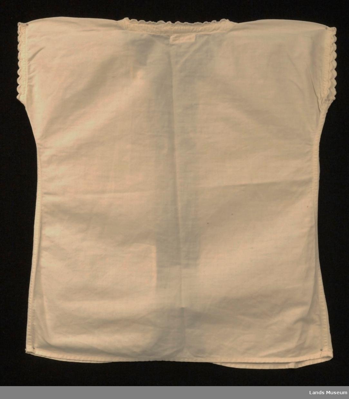 Baby-trøye utan erme, pyntet med kroklisser rundt ermehull og hals. Knytebånd i halsen.