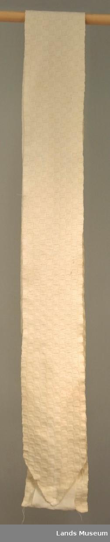 2 deler, tøystykke og strikket del. Strikket i rutemønster med 5 x 5 m og omganger i rett og vrang.