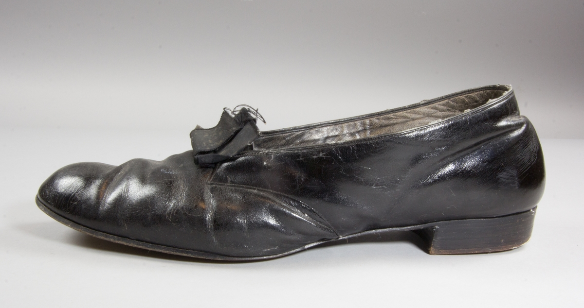 Skor, 1 par, av svart lackskinn med rosett av svart ripsband. Låg klack. Väl använda och slitna.
