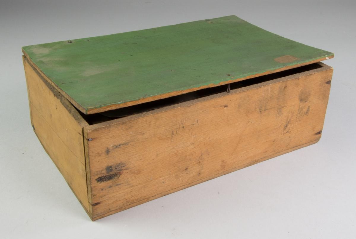 Låda av trä, rektangulär med fällock. Locket grönmålat, i övrigt omålat. Innehåller: pappersomslag innehållande silver, guld, brons repektive aluminium i bladform och pulverform samt två färgkopppar av vitt porslin med rester av guld- och bronsfärg.