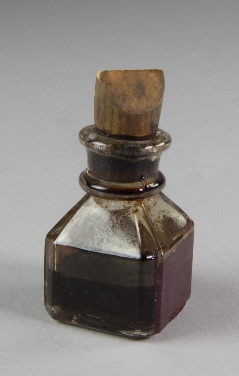 Tuschflaska av glas, kvadratisk, avfasad med kork av trä,  innehållande tusch som enligt etiketten på tyska är vattenfast för skolbruk.