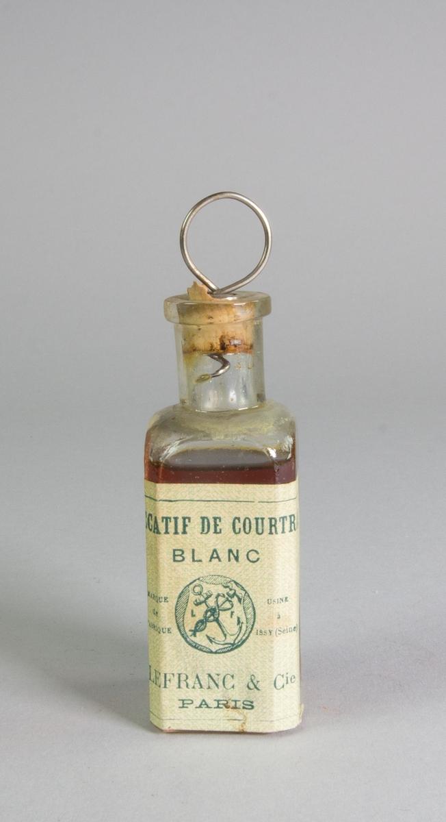 Sickativflaska av klart glas, kvadratisk, med kork med kvarsittande korkskruv av metall. Etikett. Delar av innehållet bevarat.