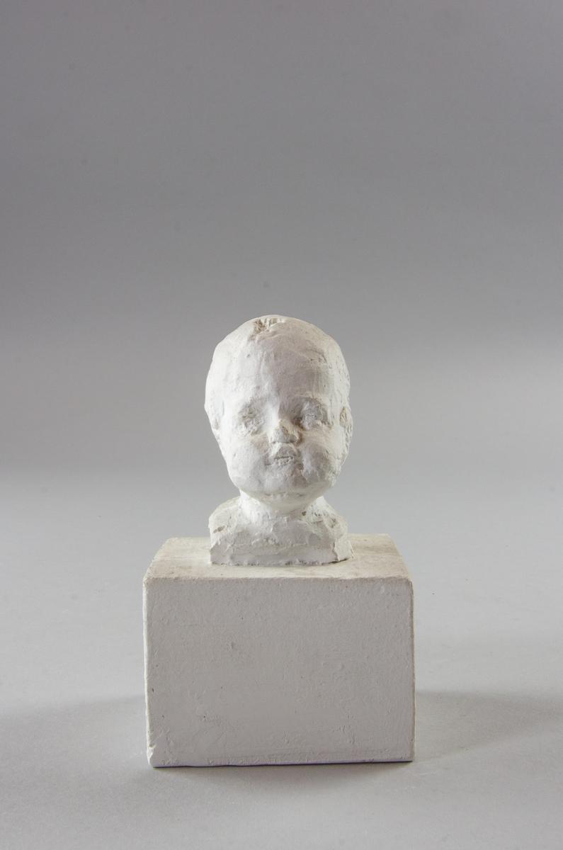 Skulpterat barnhuvud.
