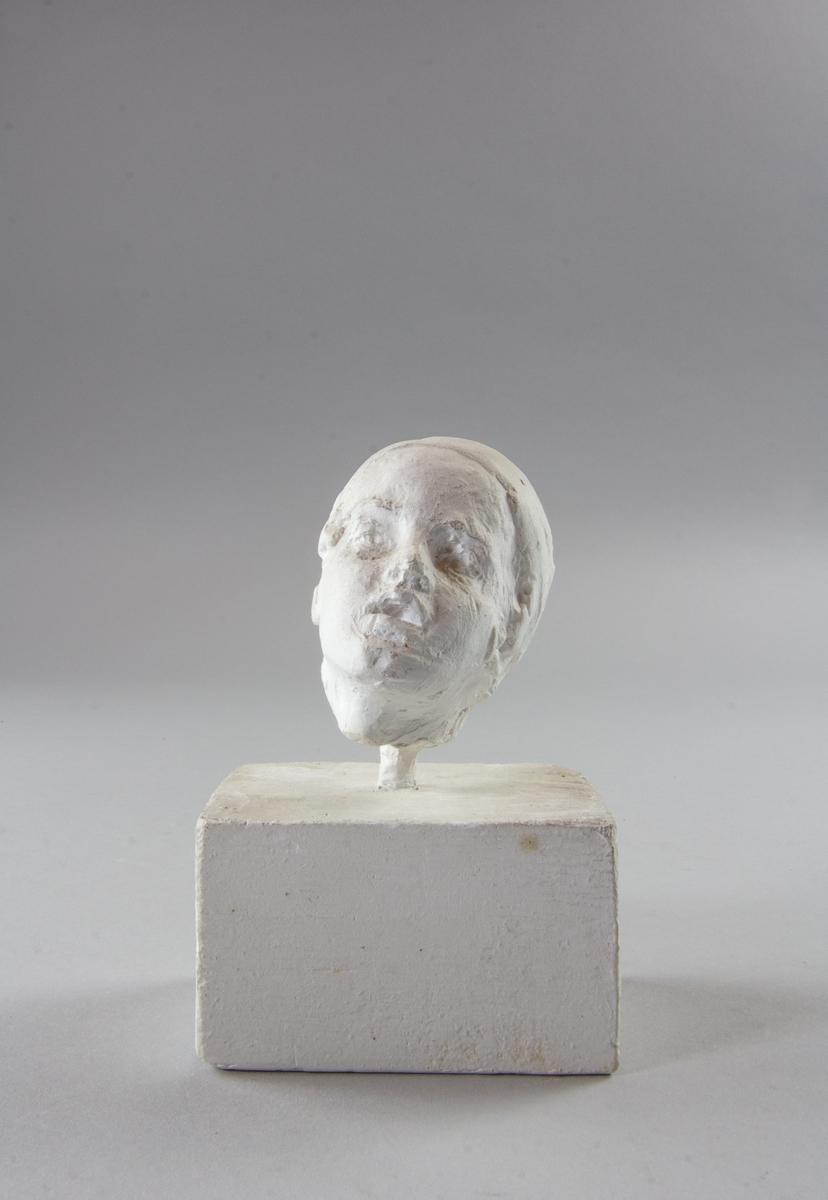 Skulpterat huvud av ung person med turbanliknande huvudbonad.