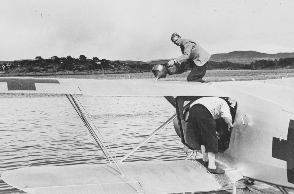 """Flyver Hans Grøn Lund ved ambulanseflyets avgang til Nord-Norge. Tekst fra album: """"Et par kanner bensin redder situasjonen."""""""